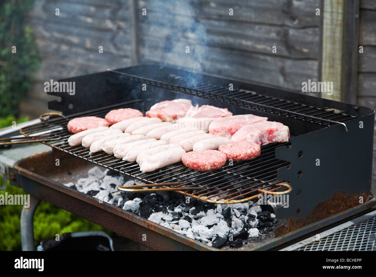 Fresh raw meat burgers sausages and pork chops cooking on a fresh raw meat burgers sausages and pork chops cooking on a barbecue grill england uk ccuart Choice Image