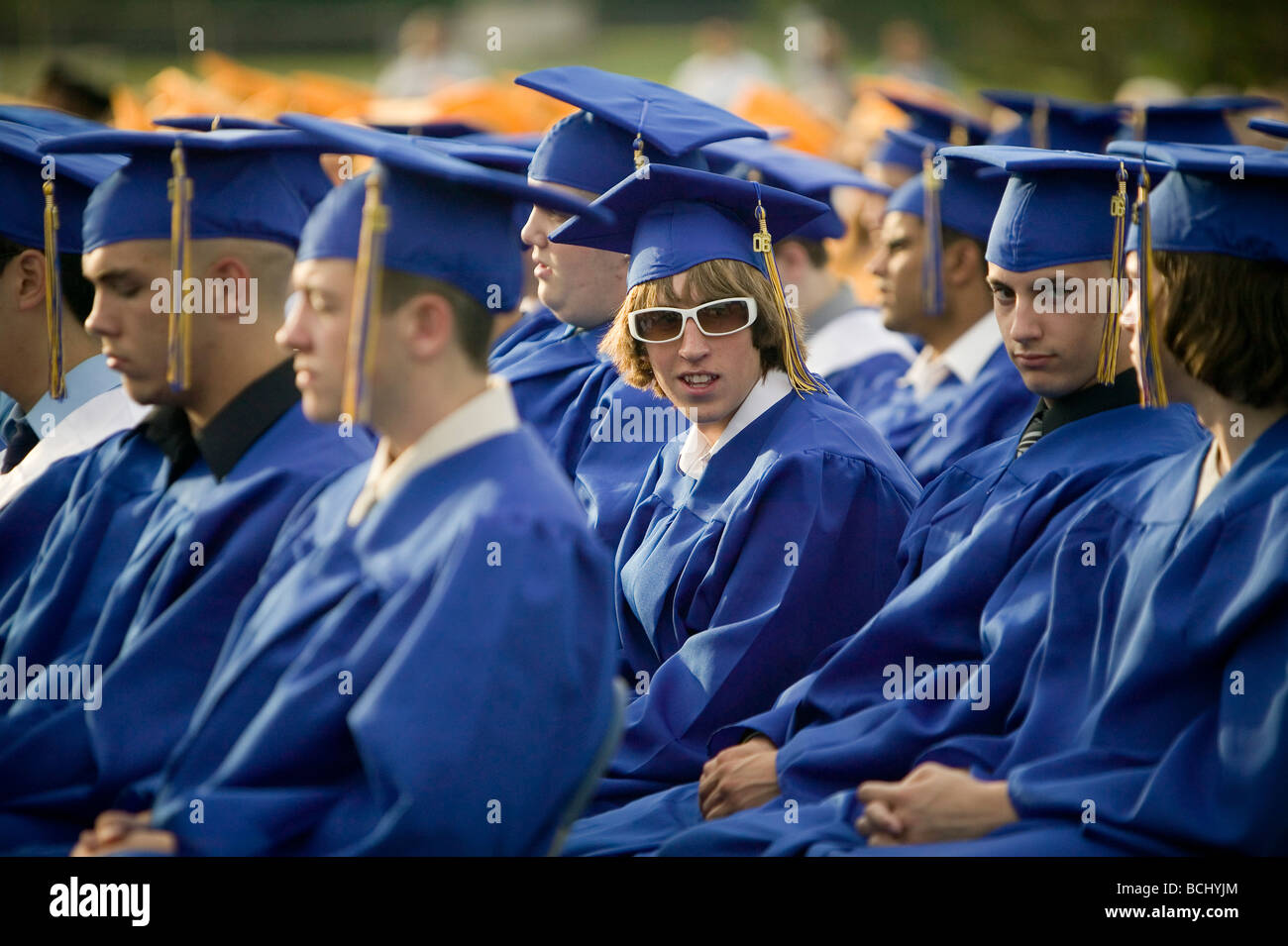 High School students wearing blue and gold cap and gown attend ...
