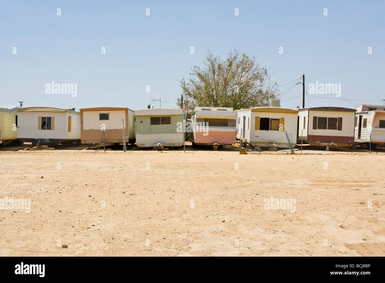 Row Of Abandoned Mobile Homes With Pastel Colors In Dirt Lot Sky Background