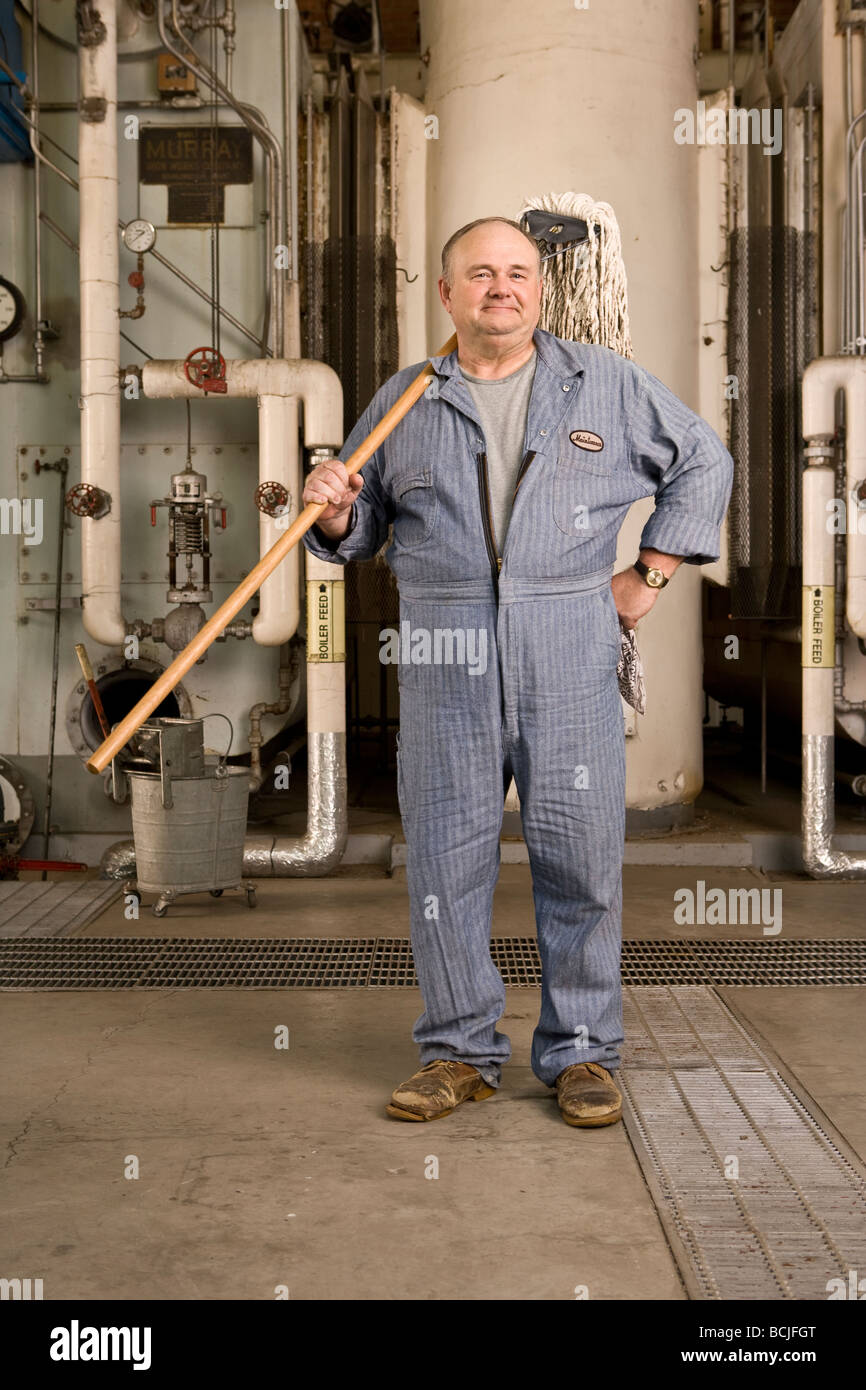 janitor stock photos janitor stock images alamy male caucasian in blue custodian janitor overalls in factory setting including boiler pipes