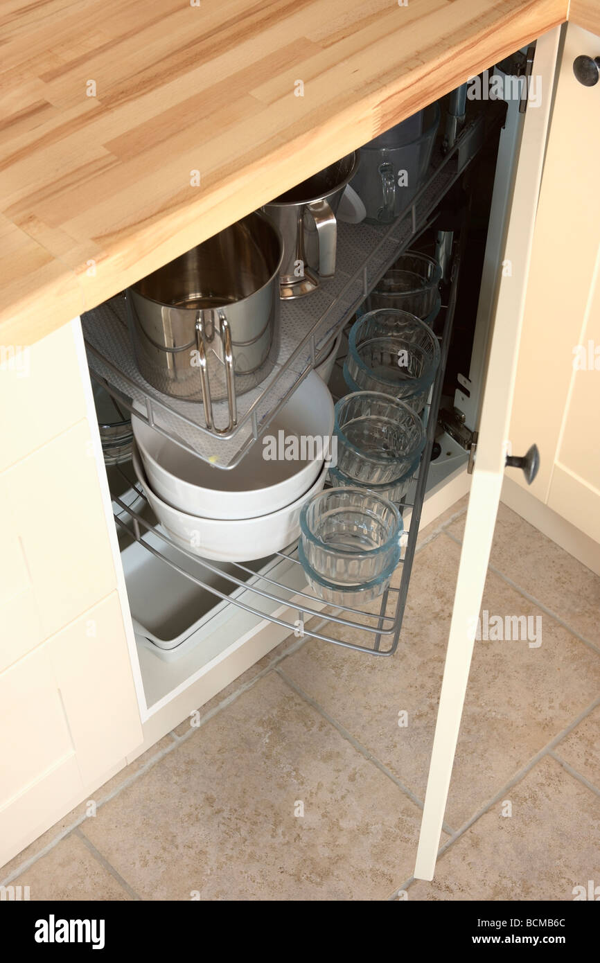 close-up of kitchen storage unit with door open to show pans and