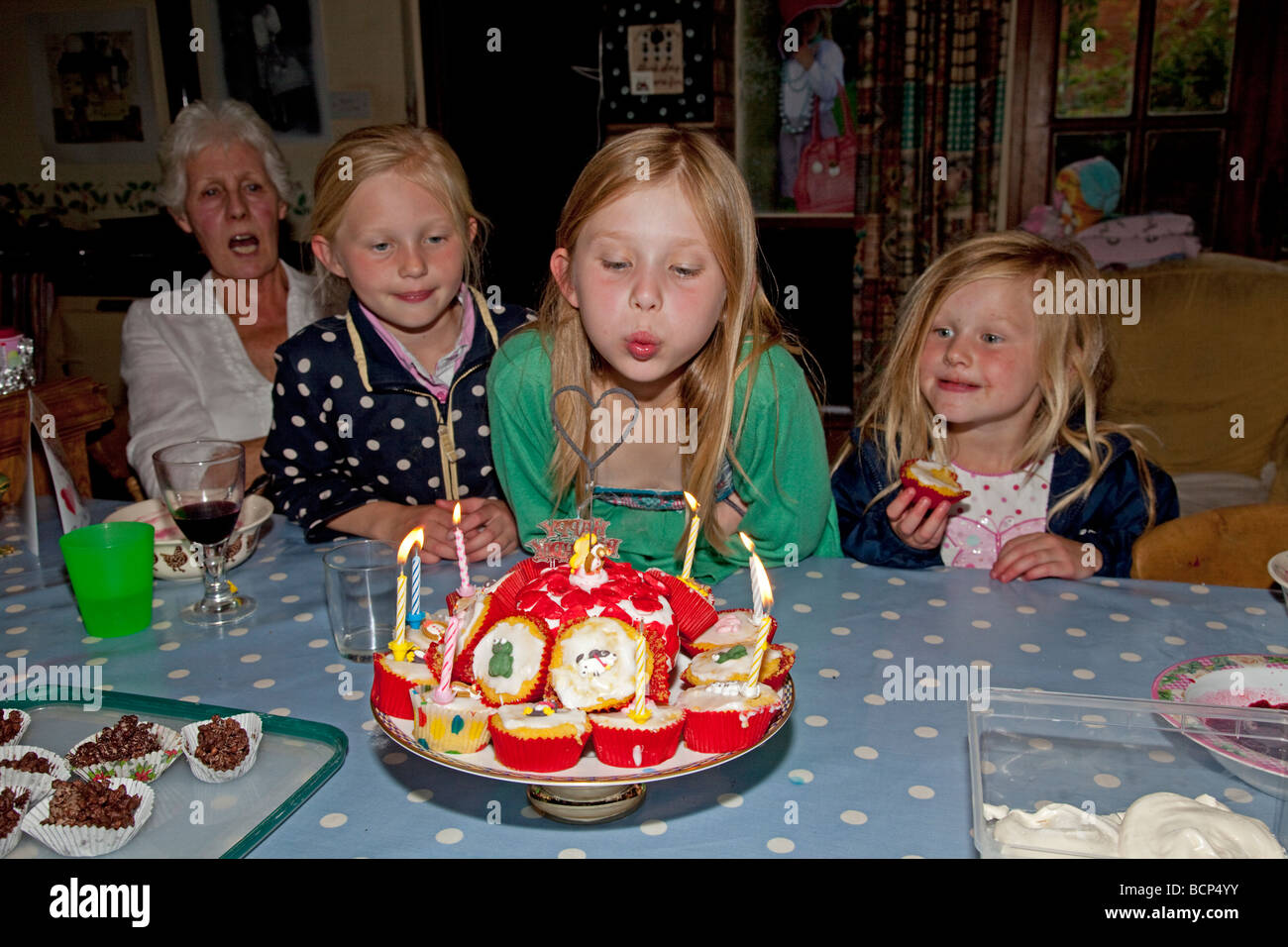 Nine Year Old Girl Blowing Out Candles On Birthday Cake