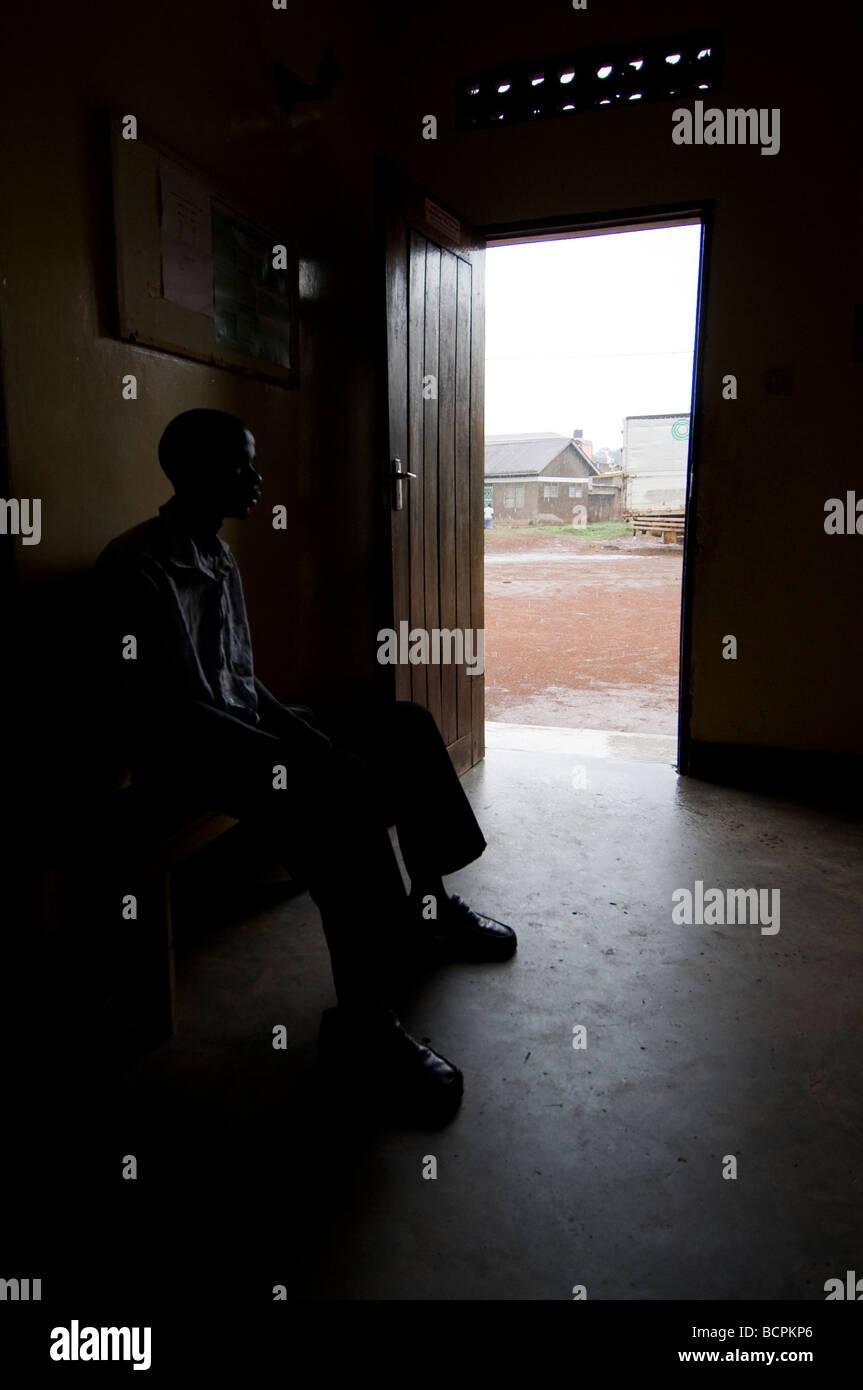 African man sitting in dark room lit by open door waiting Stock