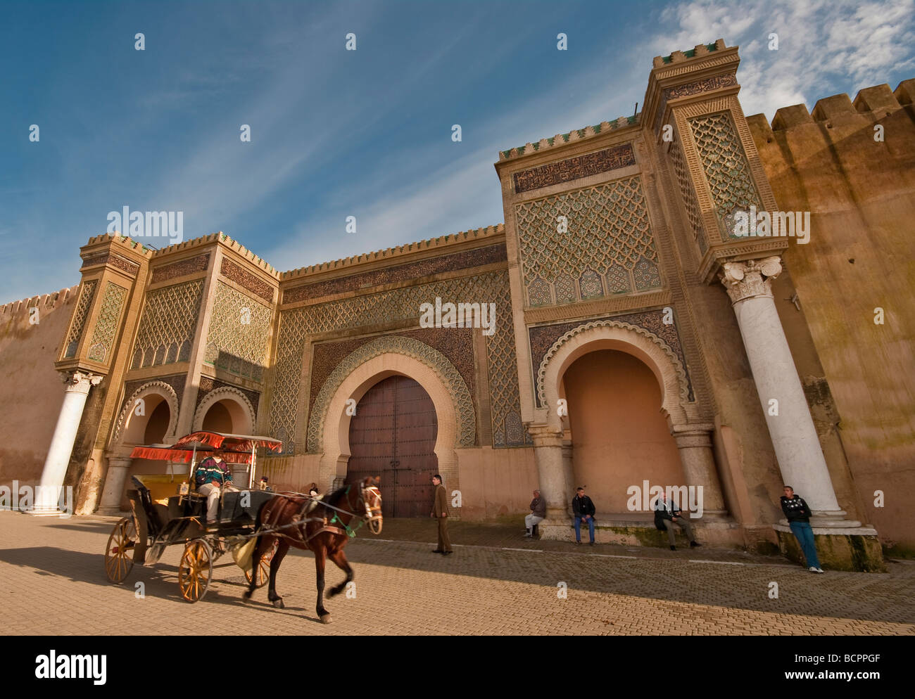 A wide angle shot of a tourist taking a carriage ride beside the famous Bab  (