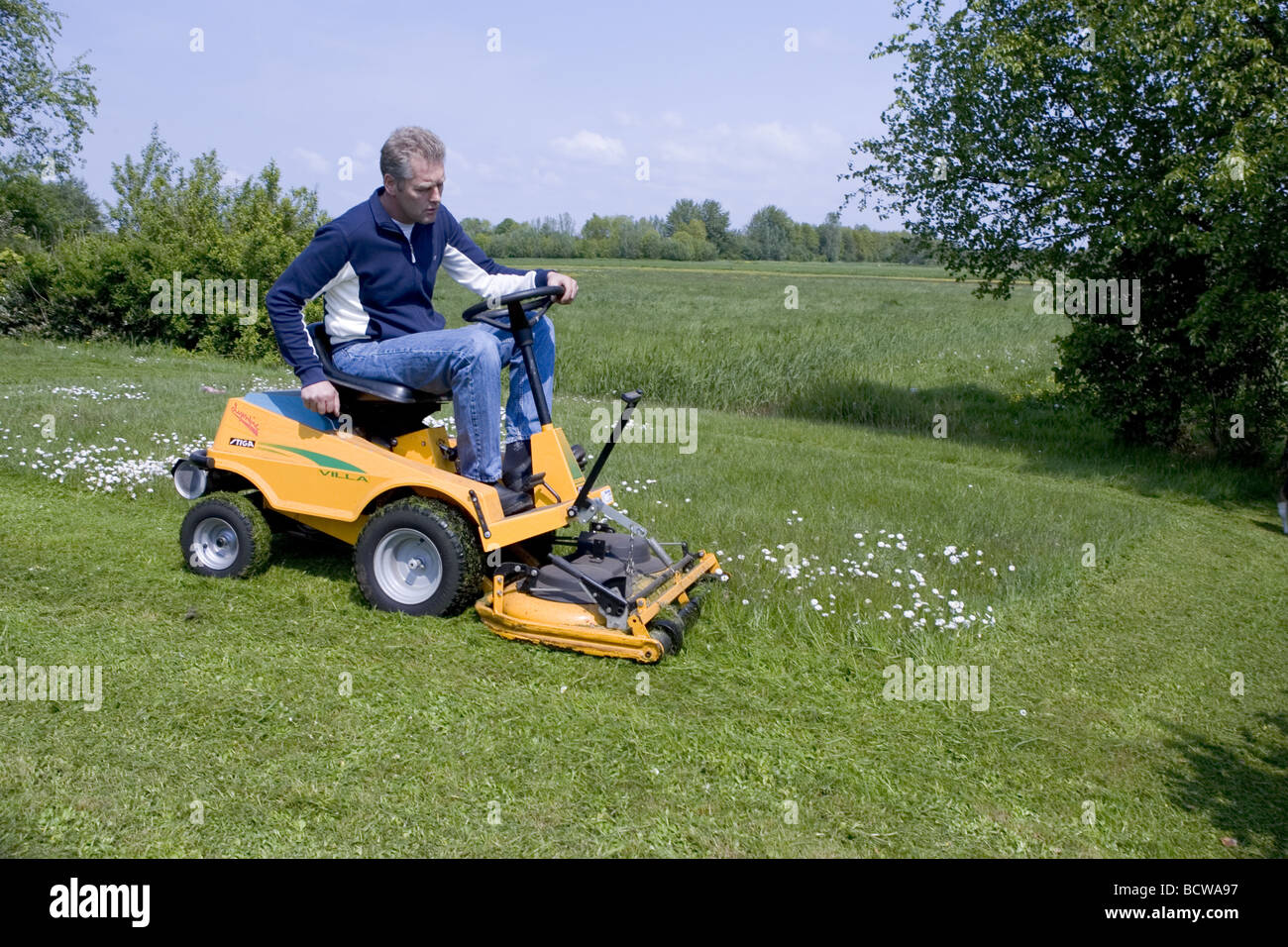 man riding lawn mower. stock photo - white man mowing suburban lawn on a riding mower