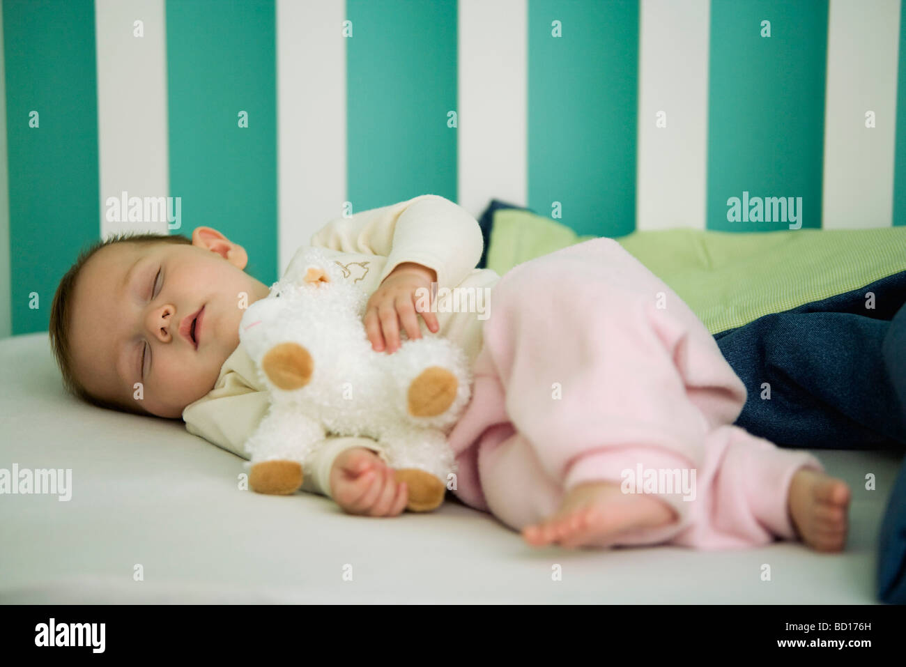 Baby Sleeping In Crib Holding Stuffed Toy Stock Photo