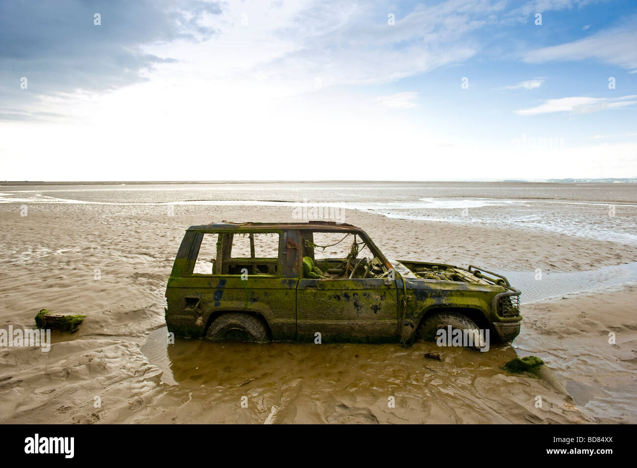 abandoned car partially buried in sand morecambe bay