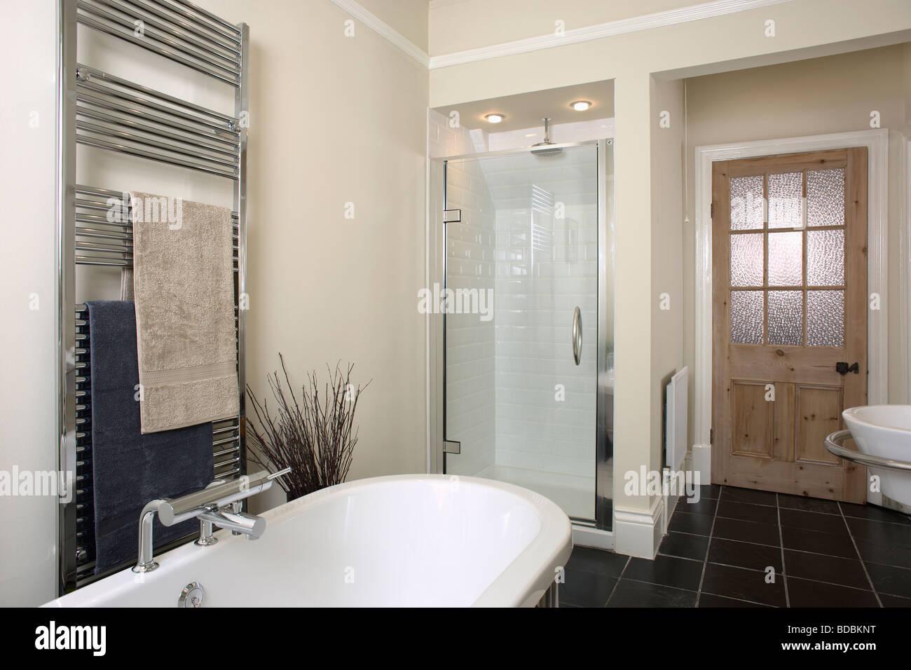 Towel rails for bathroom - Stainless Steel Heated Towel Rail Above Bath In Modern Beige Bathroom With Glass Door On Shower Unit