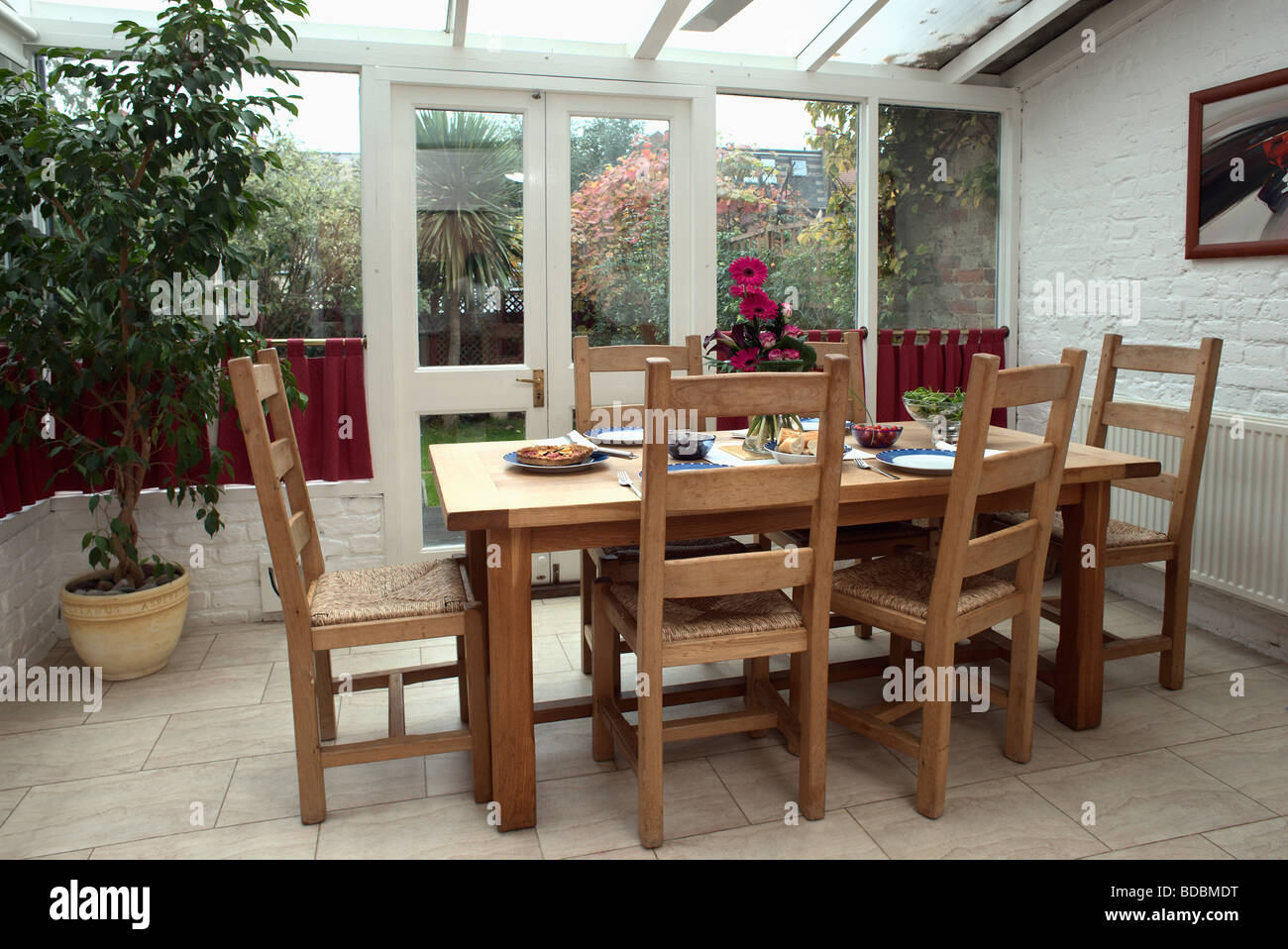 Wooden table and rush-seated chairs in conservatory dining room ...