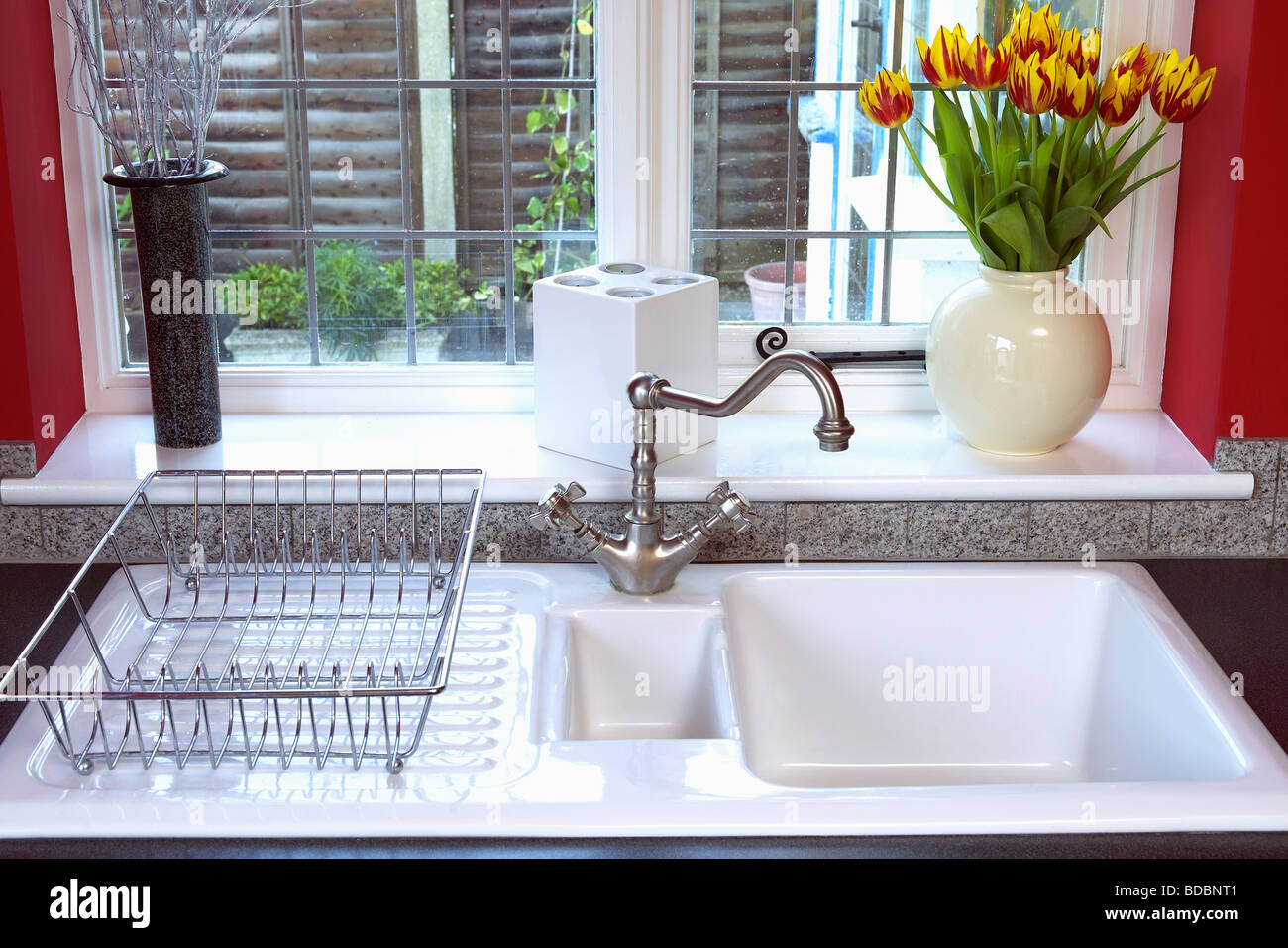 Orange Tulips In Vase On Window Sill Above White Porcelain Sink With Metal  Draining Basket And