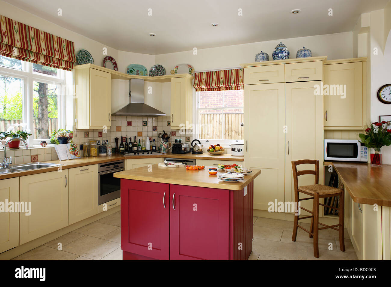 Country kitchen with fitted cream units and red island for Red fitted kitchen