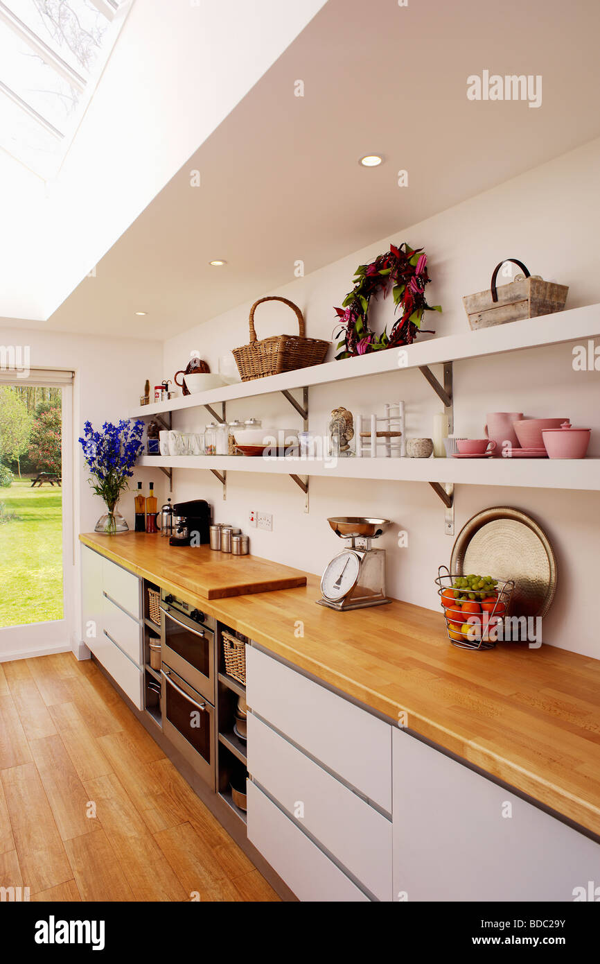 White Kitchen With Wooden Worktops wooden worktop on fitted white unit below open white shelves in