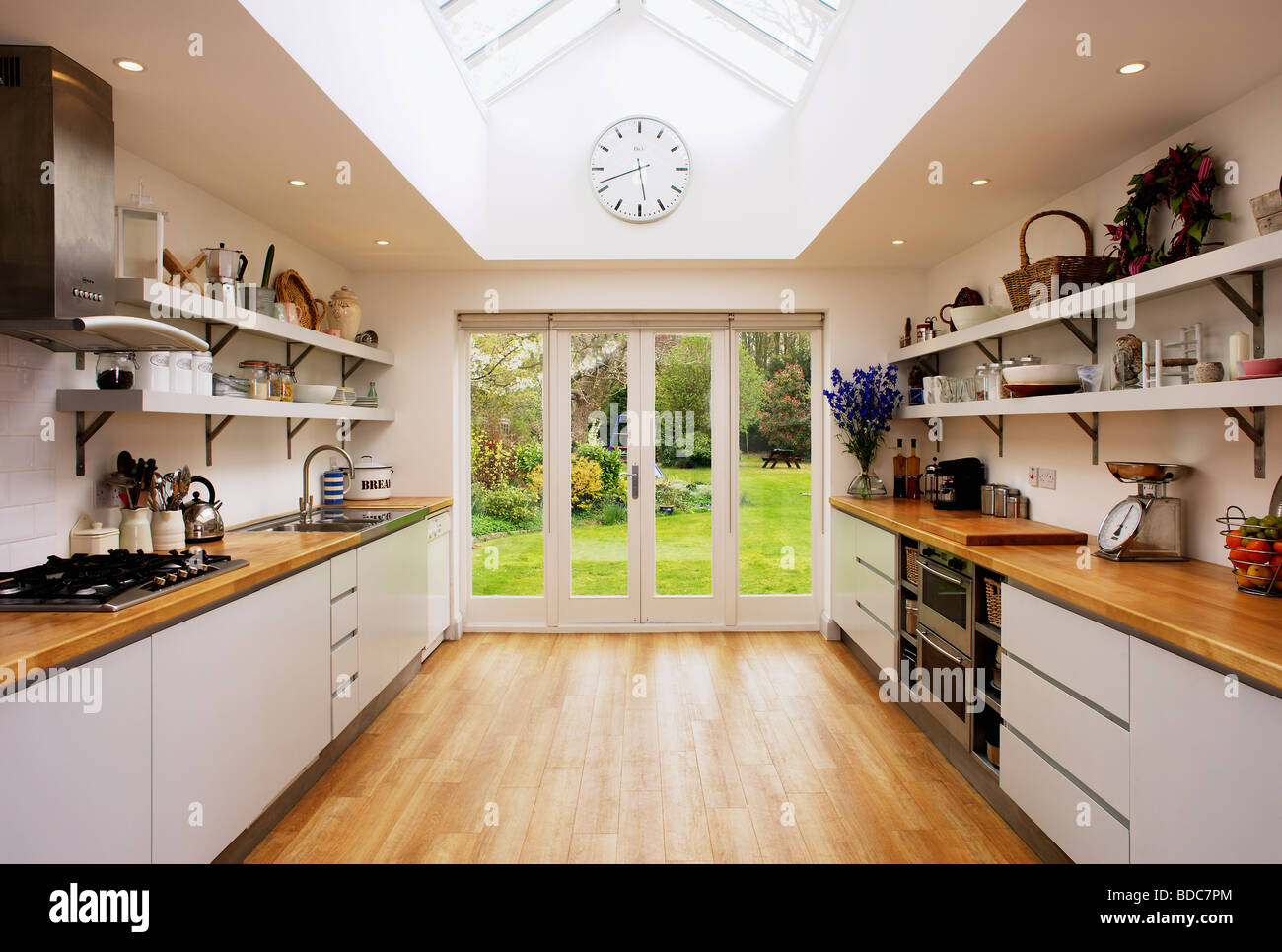 Stock Photo   Wooden Flooring And Glass Patio Doors In Modern Kitchen  Extension With Fitted White Units