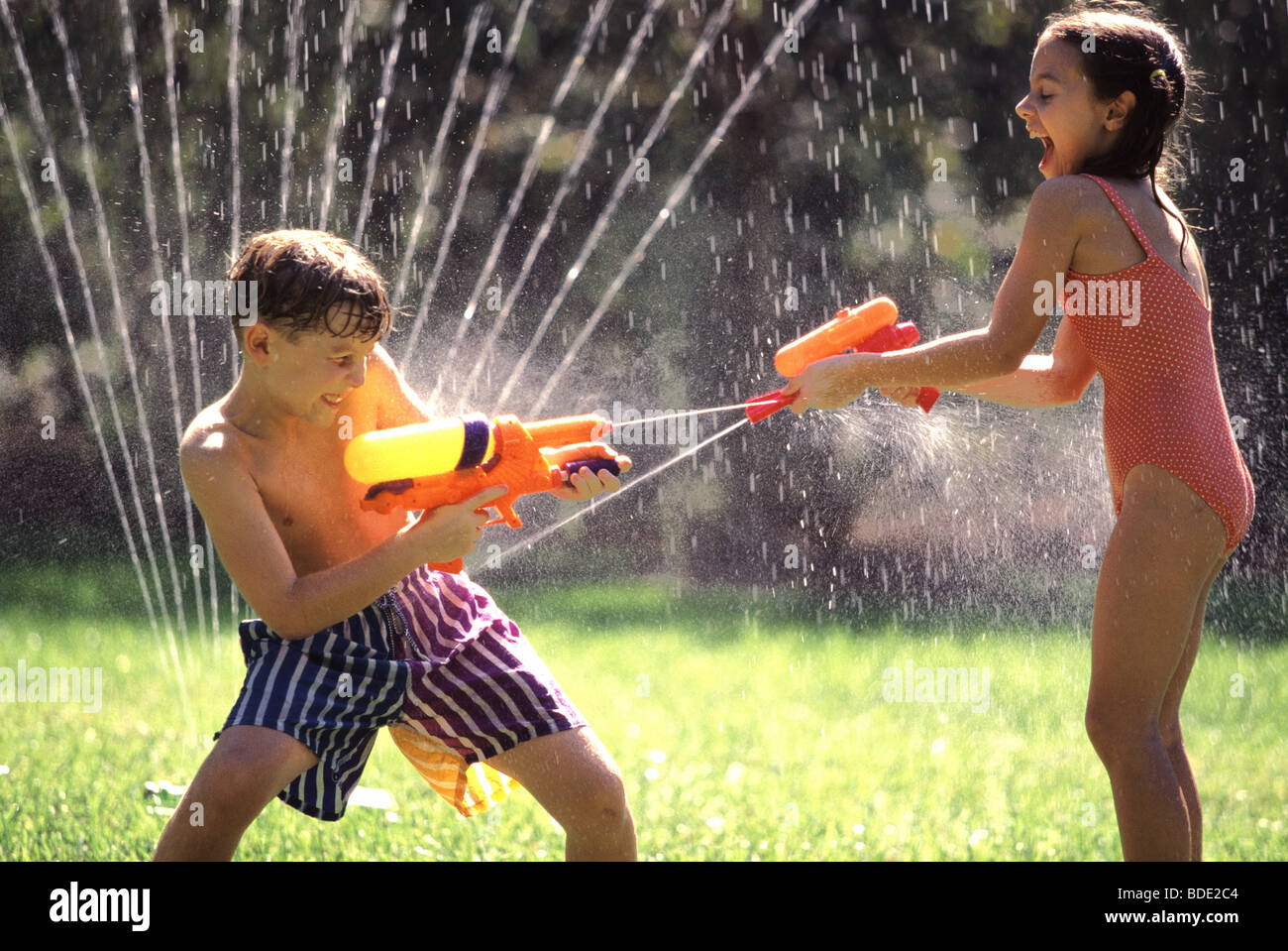 kids play water Kids playing with squirt guns on a summer day. - Stock Photo