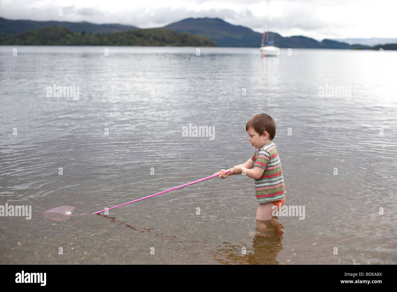 A four year old boy with a pink fishing net paddles in for Take me fishing org