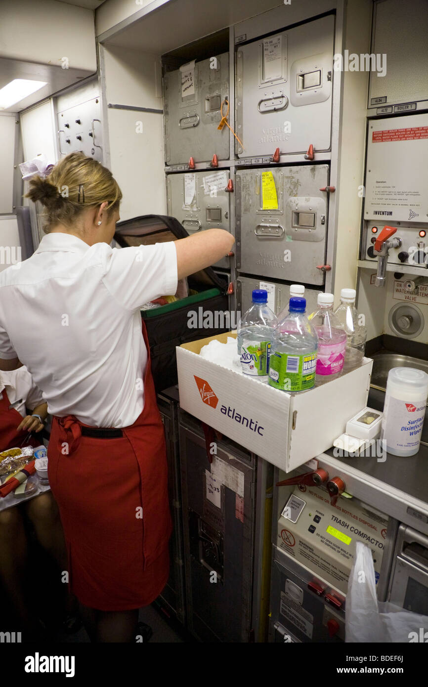 Member Of Cabin Crew With A Box Of Soft Drinks On A Virgin