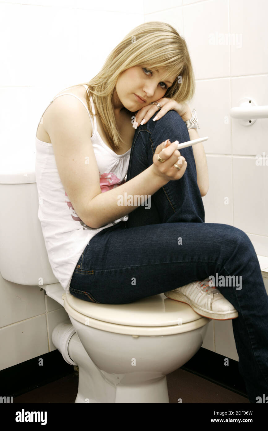 young teenage girl sitting on a toilet with one knee up