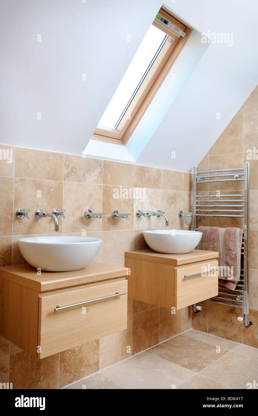 A MODERN BATHROOM WITH TWIN SINKS AND VELUX ROOF WINDOW