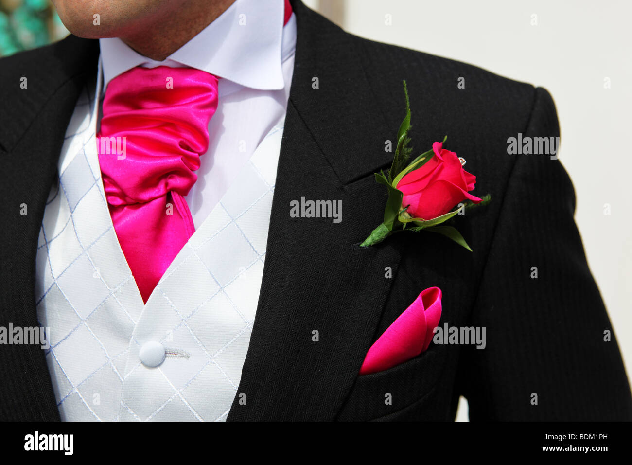 Closeup detail of colourful pink button hole on groom\'s wedding ...
