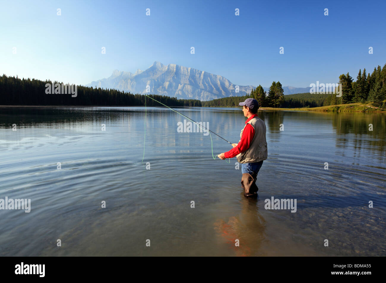 Middle age man fly fishing in two jack lake banff for Fishing in banff