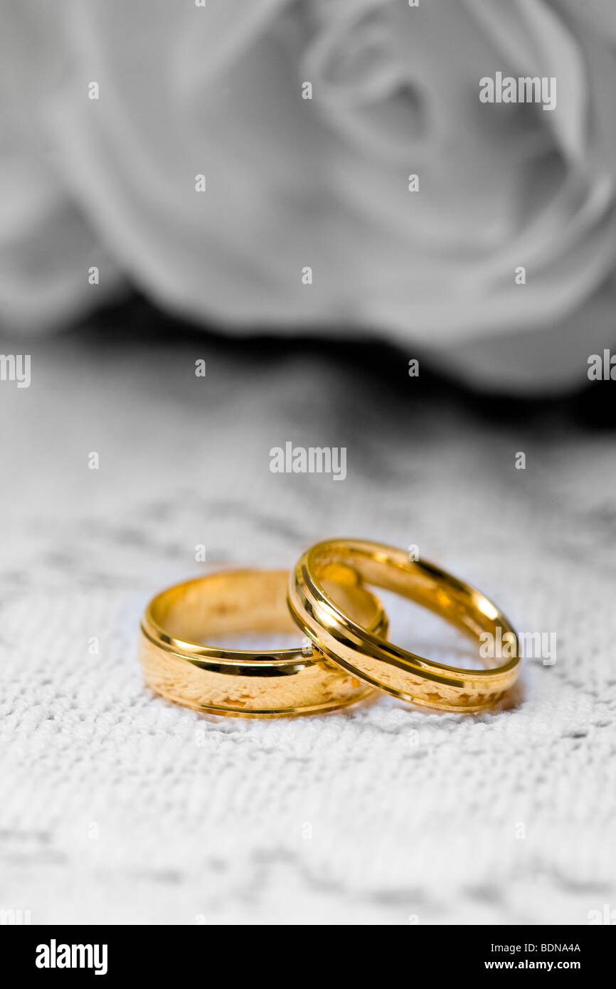 two gold wedding rings with a digitally altered black and