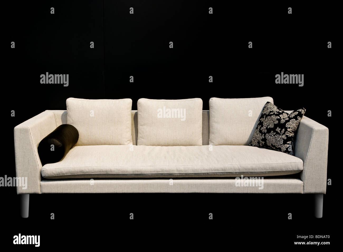 a white designer sofa on black background