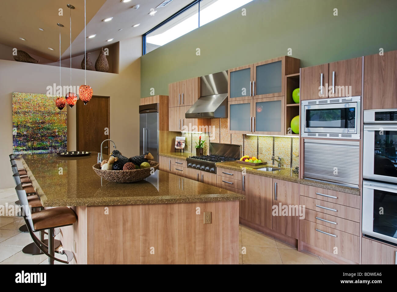 sideview of ultra modern high ceiling kitchen with granite center