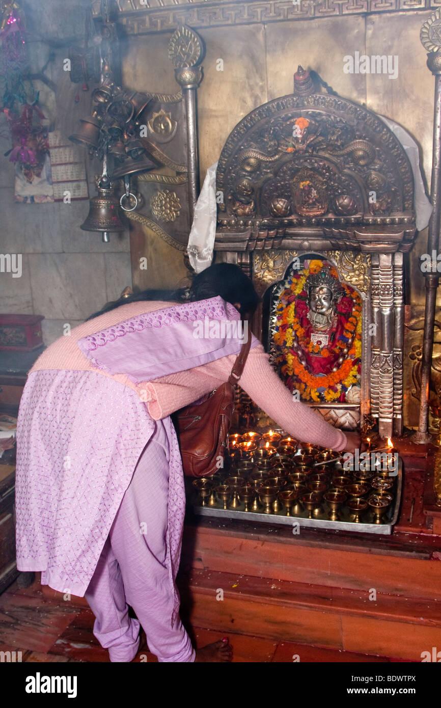 nepalese woman lighting alter candles at the shrine of ajima goddess of smallpox alter lighting
