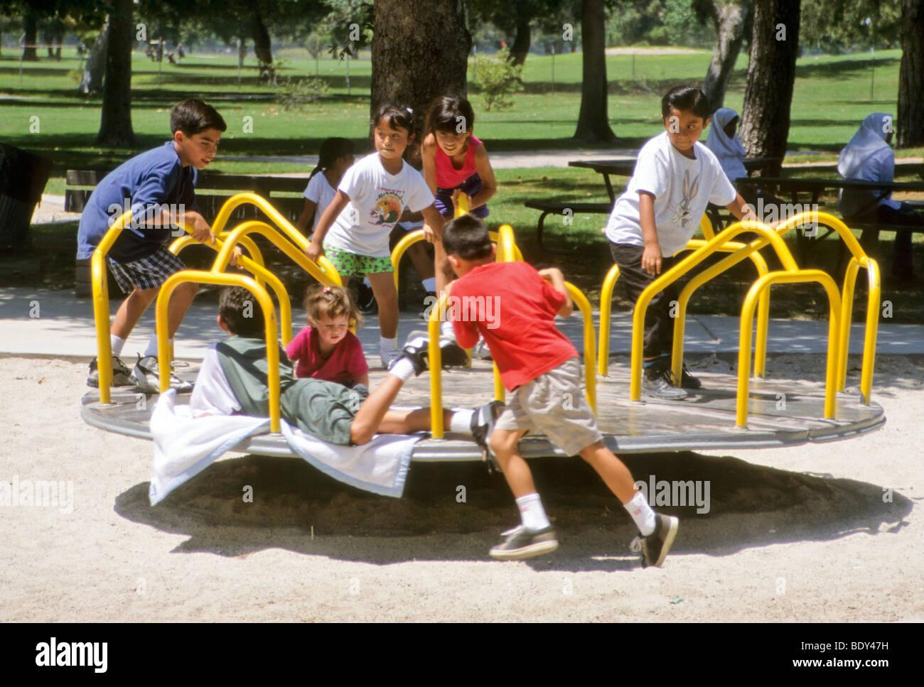 Children Spin On Merry Go Round In Park Playground