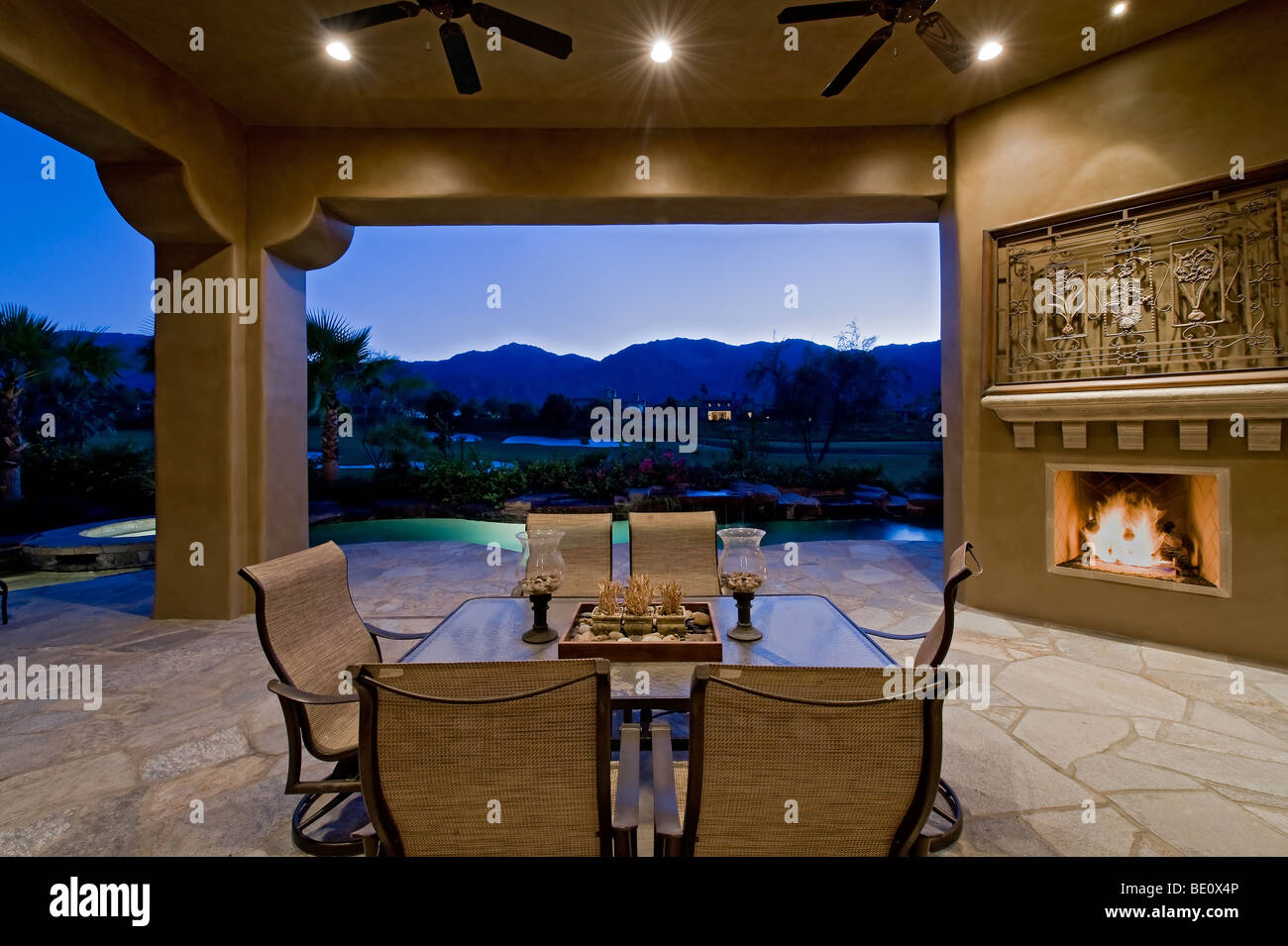 Outdoor sitting area with fireplace overlooks mountain view back ...