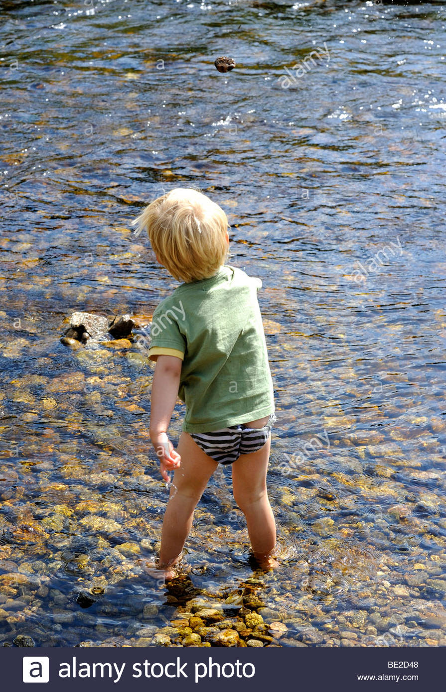 naked boy in river A young naked boy throwing stone into the river