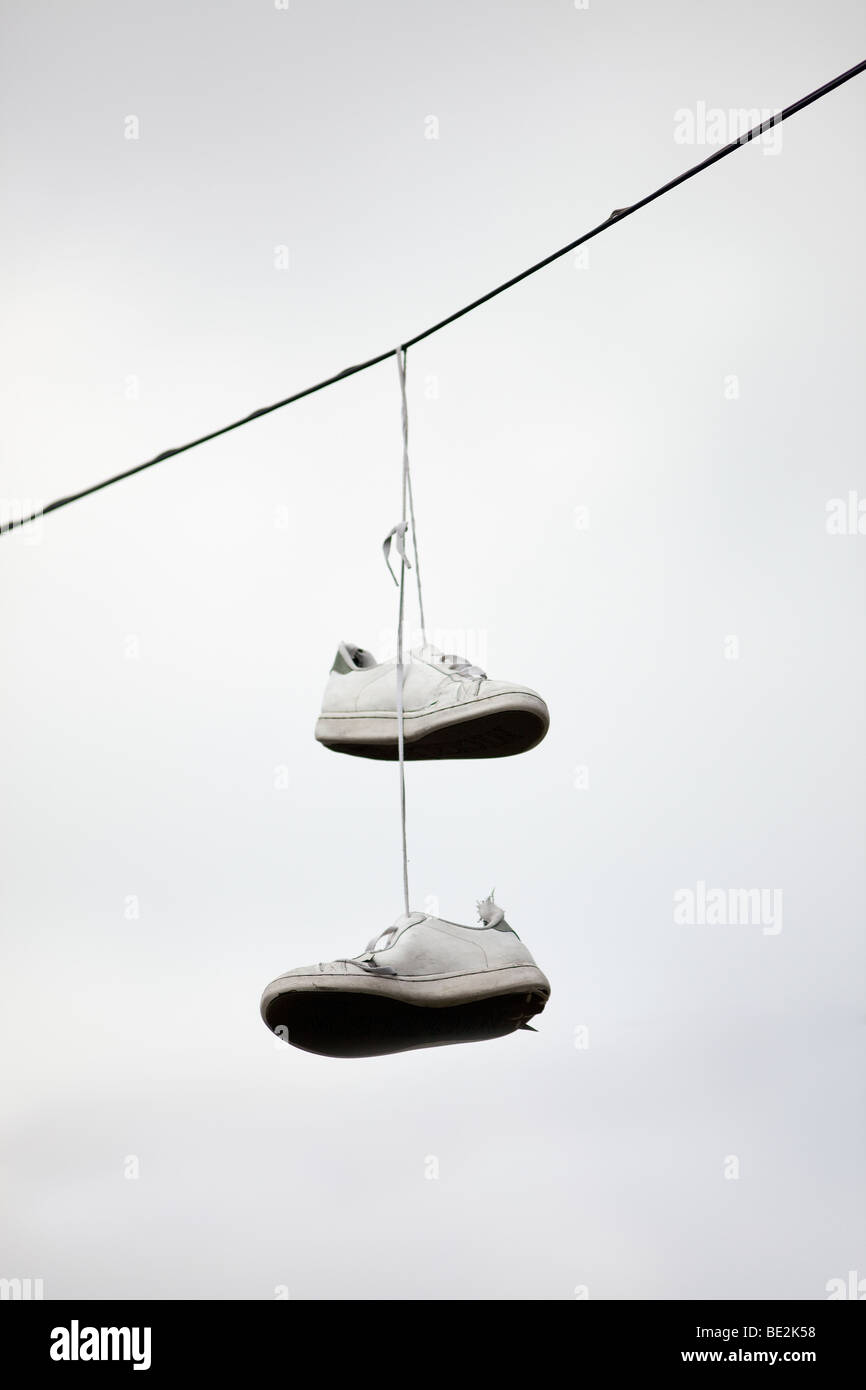A pair of trainers hanging from a telephone wire for Hang photos from wire