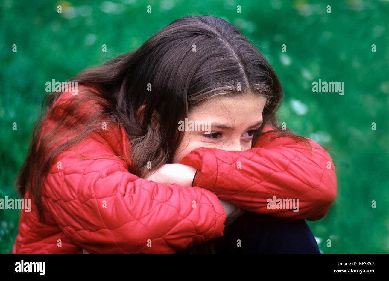 Teenage girl distressed , head in her arms, depressed ...