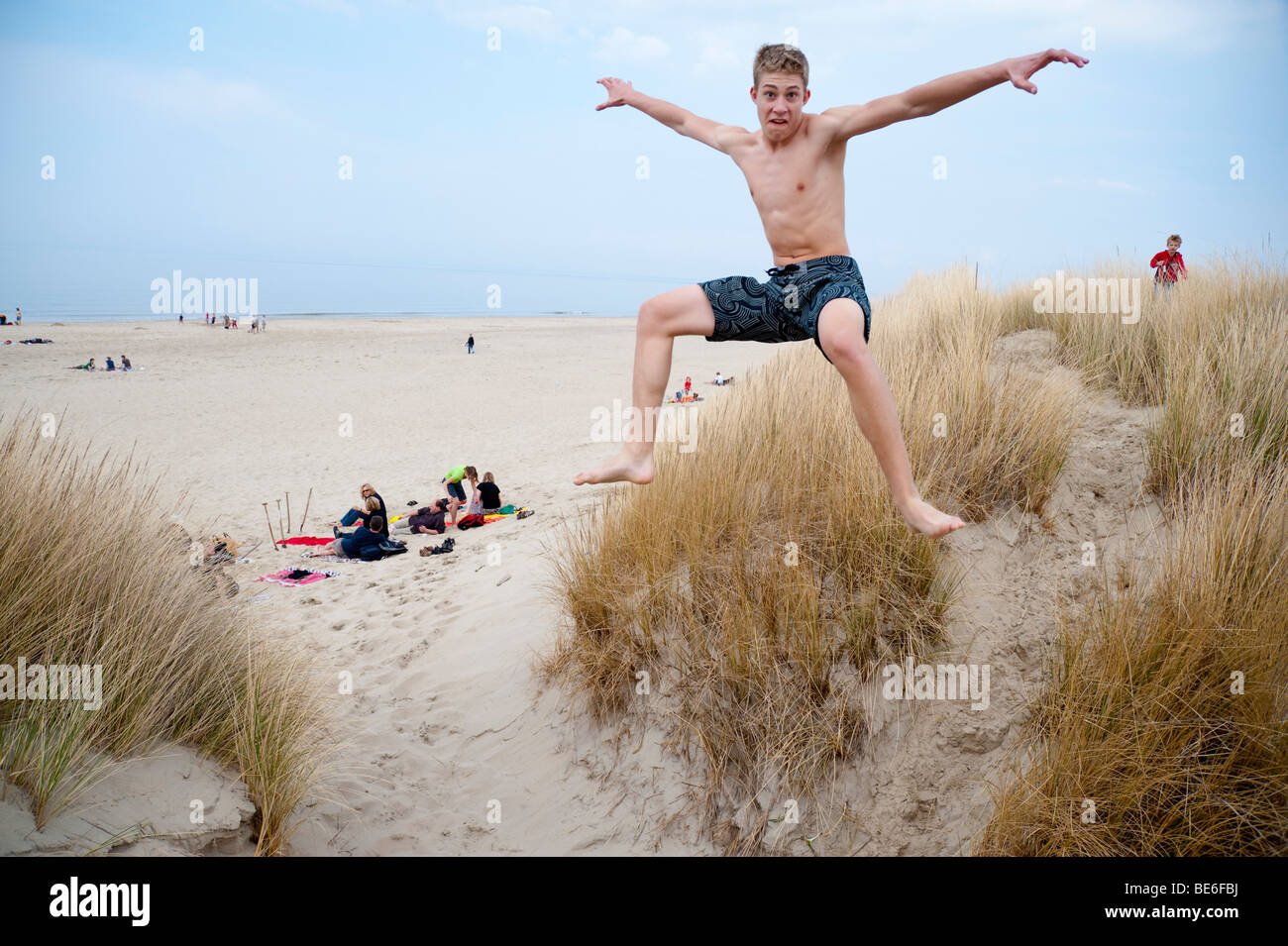 A 16 Years Old Boy Jumps From A Sand Dune At The North Sea