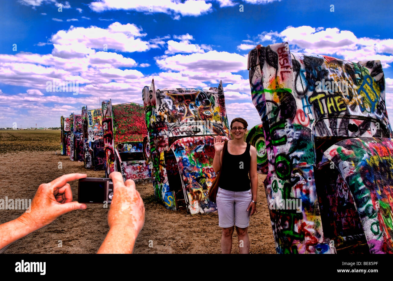 Stock photo tourist taking picture with camera at the cadillac ranch with buried cars in ground in amarillo texas usa
