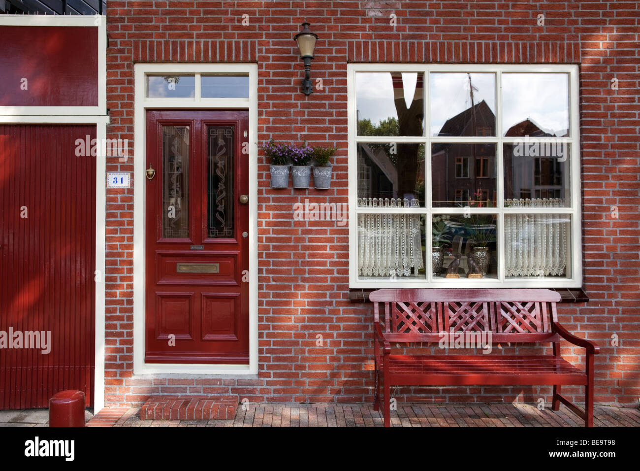 Red Brick House Front With Red Bench And Red Front Door