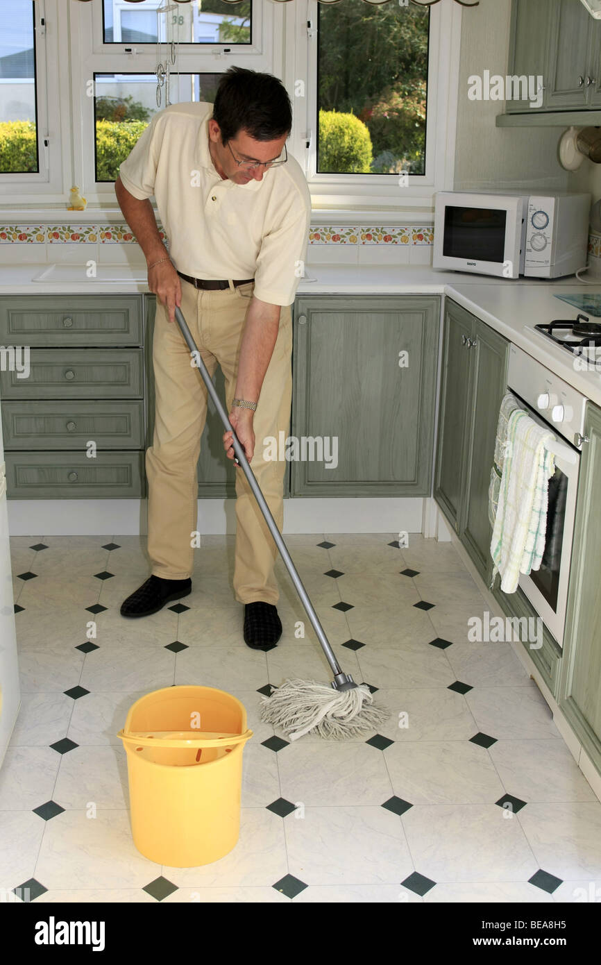 A Man Using A Mop And Bucket To Clean A Kitchen Floor
