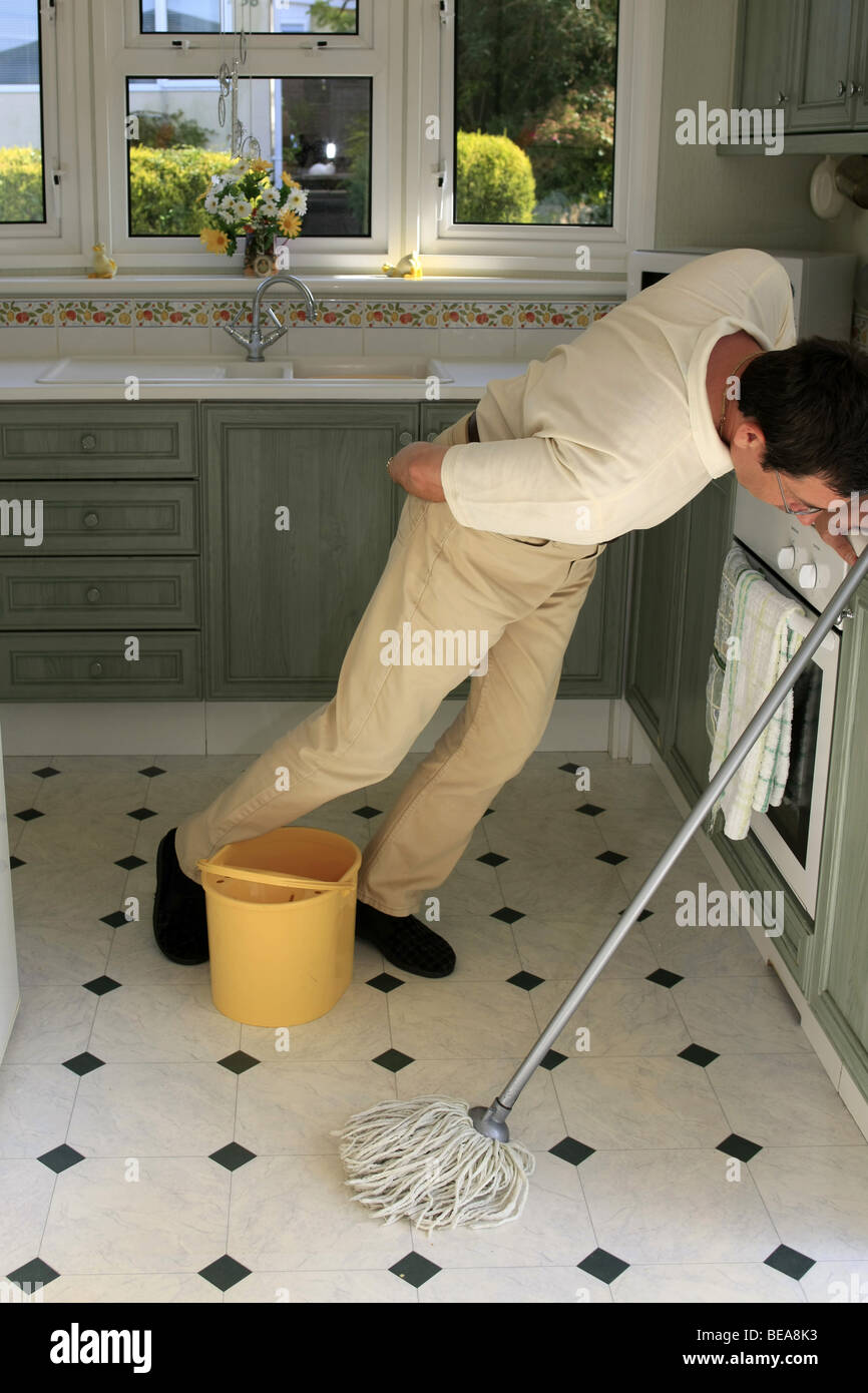 Kitchen Floor Mop A Man Using A Mop And Bucket To Clean A Kitchen Floor Stock Photo