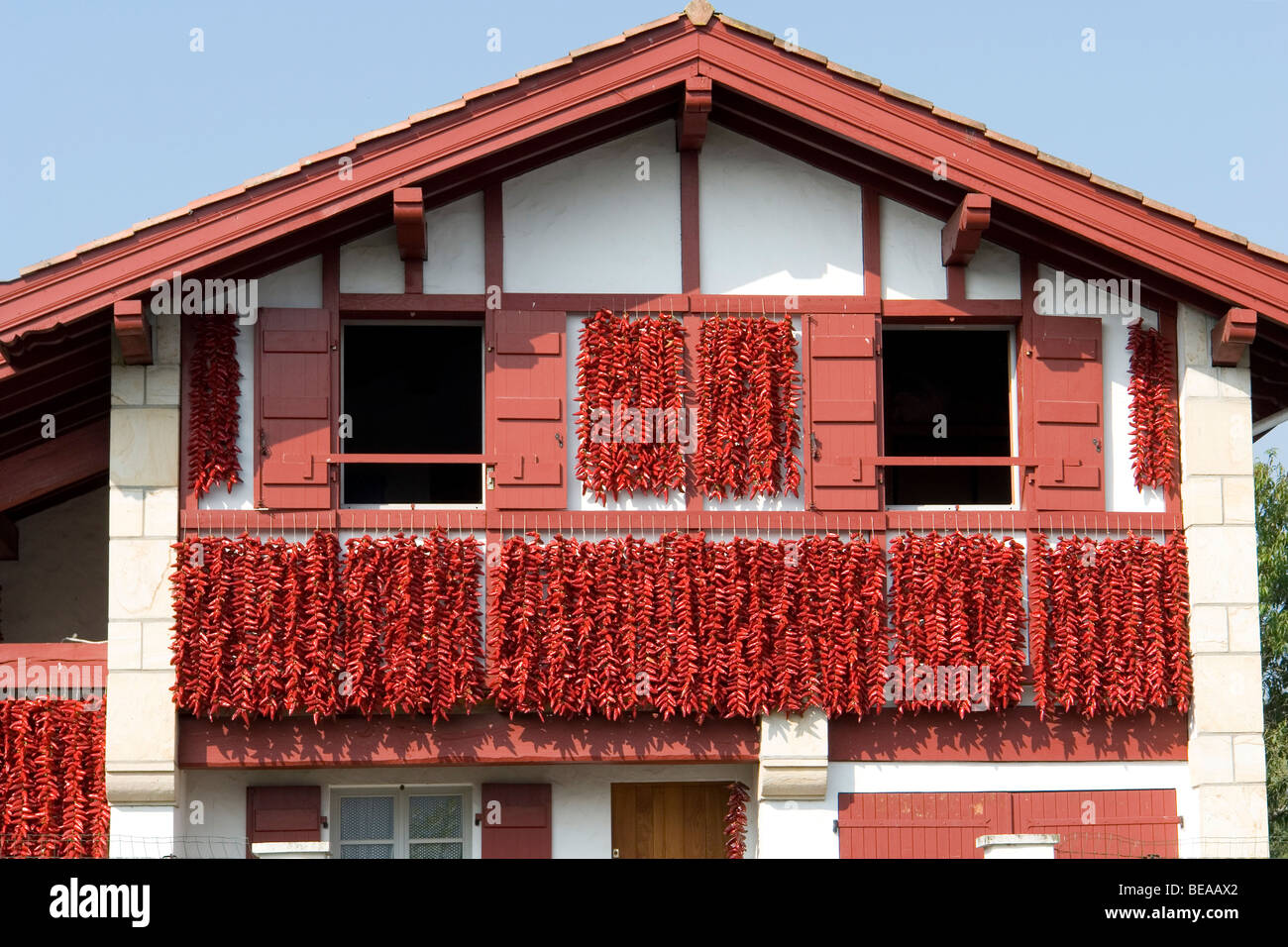 Red peppers drying on the frontage of a basque house espelette stock photo royalty free image for Photos maison basque