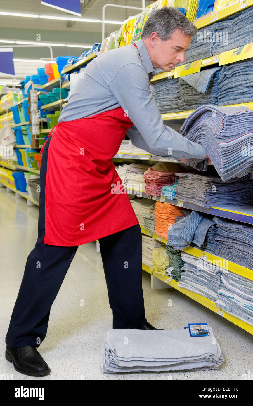 s clerk arranging clothes in the shelf of a supermarket stock s clerk arranging clothes in the shelf of a supermarket