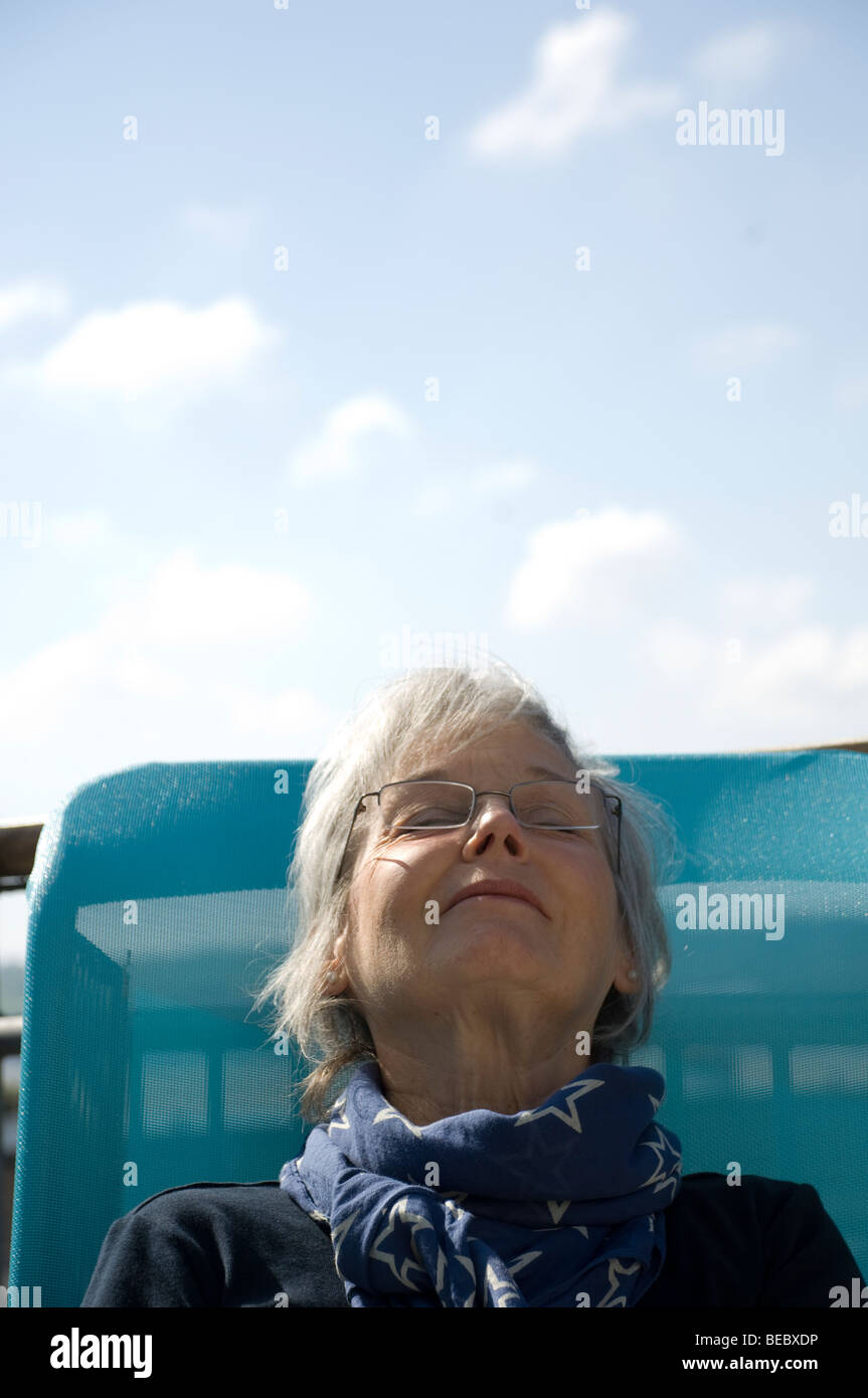 Mature Woman Sitting On A Sunlounger At The Seaside Stock Photo ...
