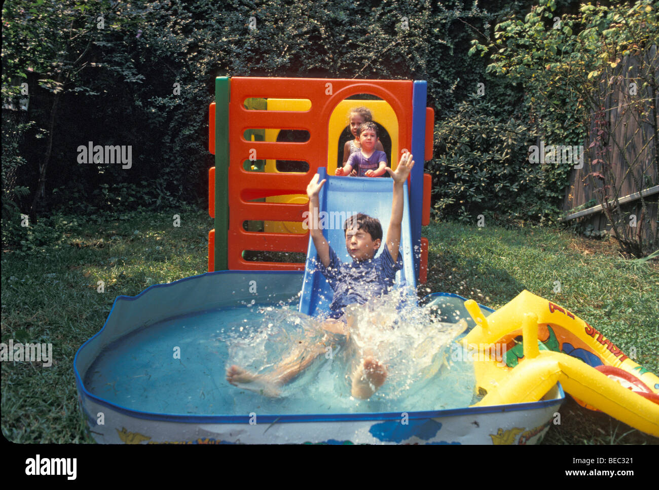 kids have fun on a homemade water slide in the backyard in