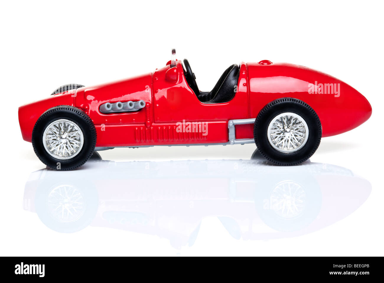 Old fashioned red toy racing car on a white background with Stock ...