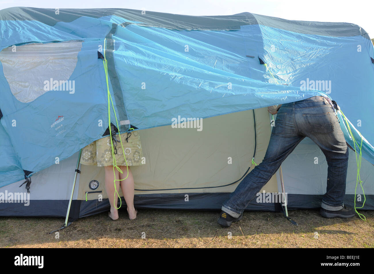 A couple struggle with the erection of a large tent & A couple struggle with the erection of a large tent Stock Photo ...