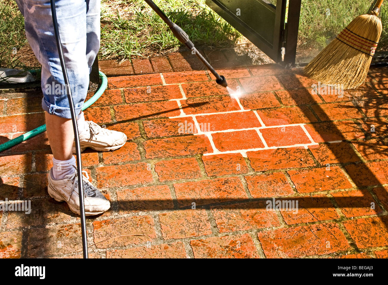 Stock Photo   Woman Cleaning A Brick Patio With A Pressure Washer