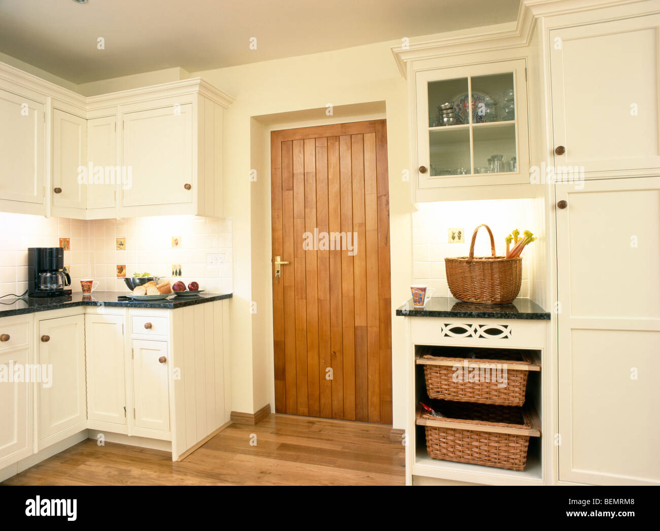Stock Photo Storage Baskets In Fitted Unit Beside Wooden Door In Cream Country Kitchen