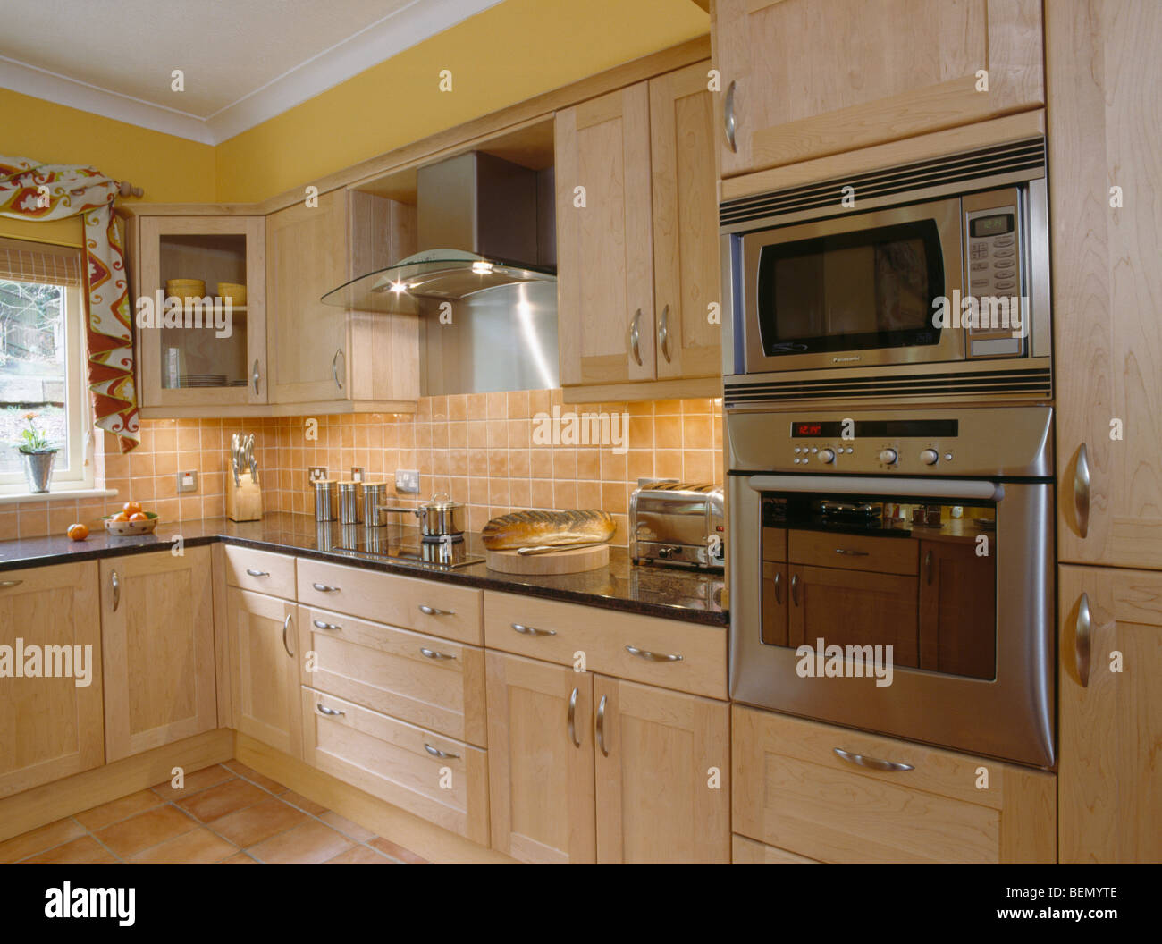 Pale Orange Kitchen eye-level oven and microwave in modern yellow kitchen with pale