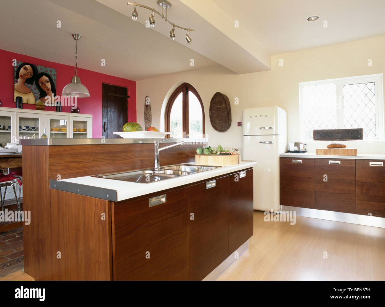 Pink wall in large modern cream kitchen with dark wood for Large kitchen wall units