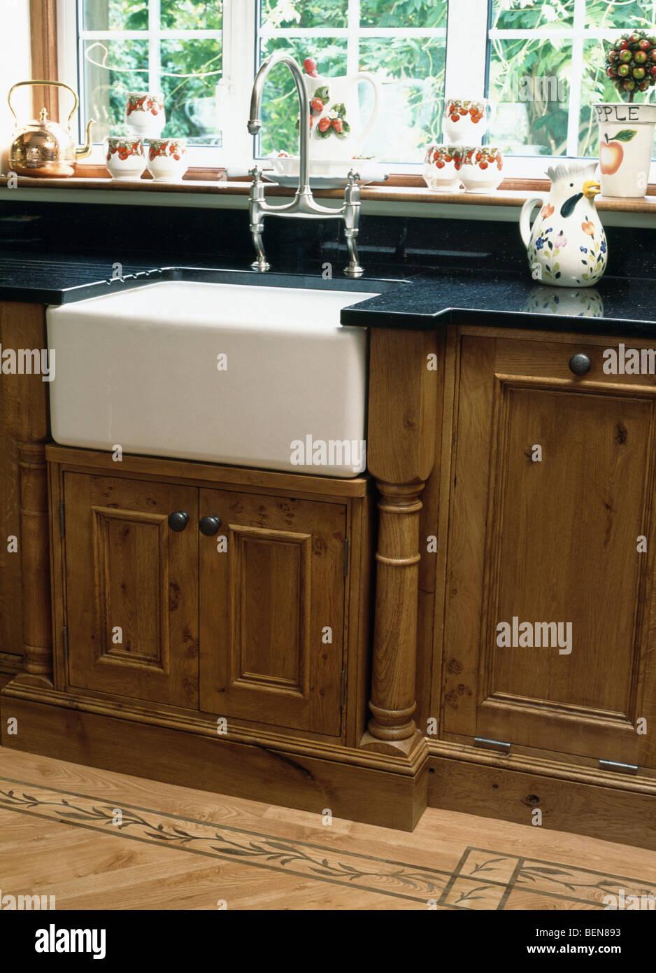 Belfast sink below window in fitted oak kitchen unit Stock Photo ...