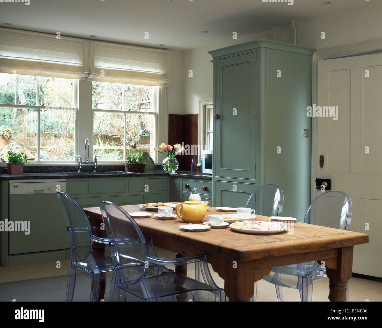 philippe starck ghost chairs at old pine table in country kitchen with fitted turquoise units and - Philippe Starck Kitchen